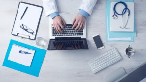 Medical assistant typing on laptop