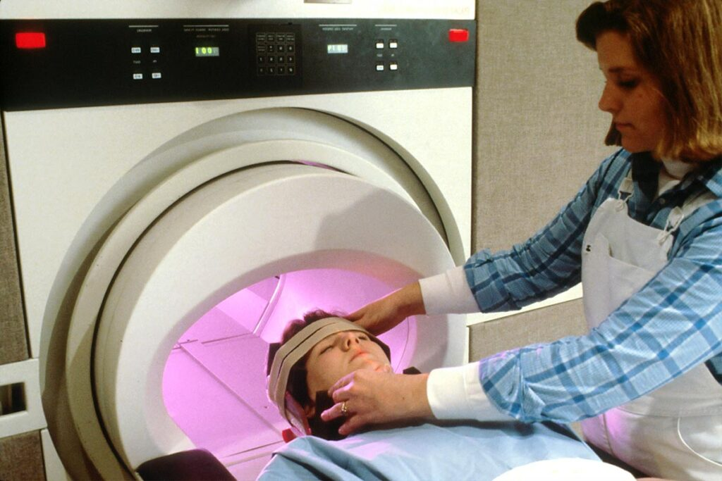 MRI technologist adjusting patient